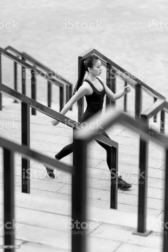 Young sporty asian woman in sportswear jogging on stadium stairs, black and white photo stock photo
