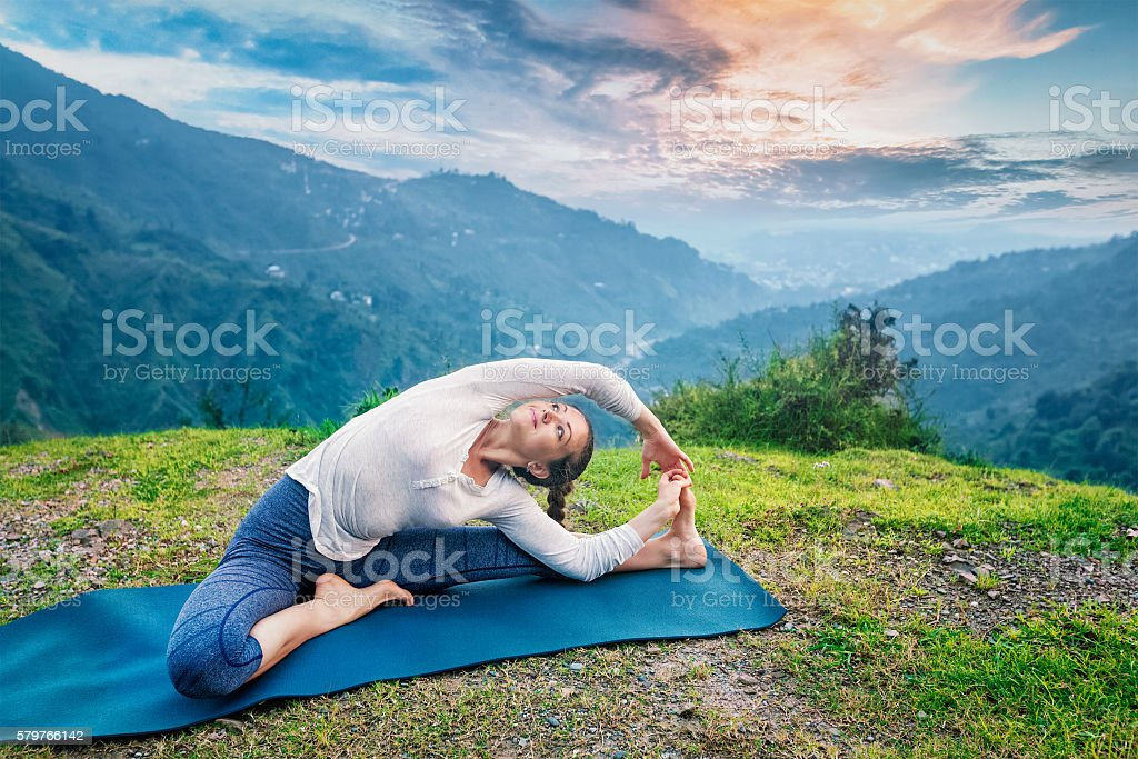 Young sporty fit woman doing Hatha Yoga asana in mountains stock photo