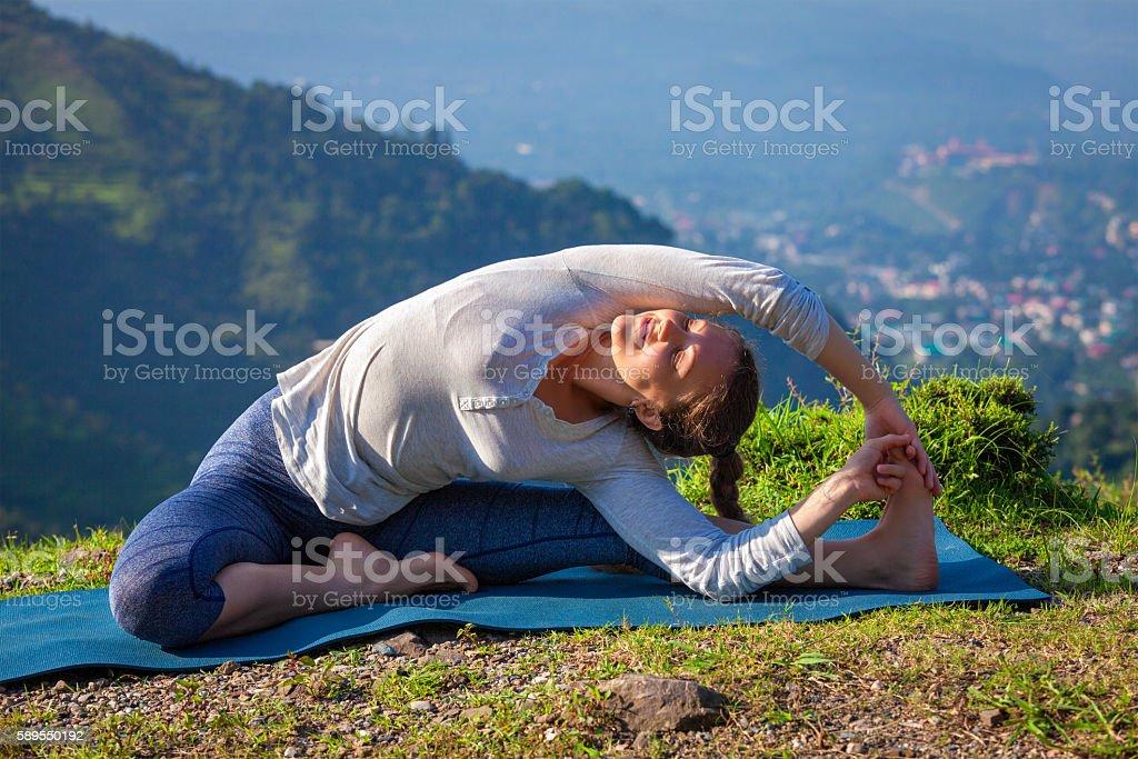 Young sporty fit woman doing Yoga asana parivritta janu sirsasana stock photo