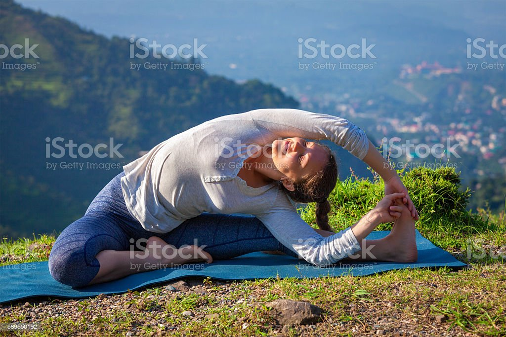 Young sporty fit woman doing Yoga asana parivritta janu sirsasana stock photo