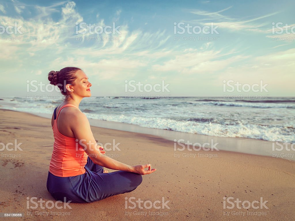 Young sporty fit woman doing yoga oudoors at beach stock photo