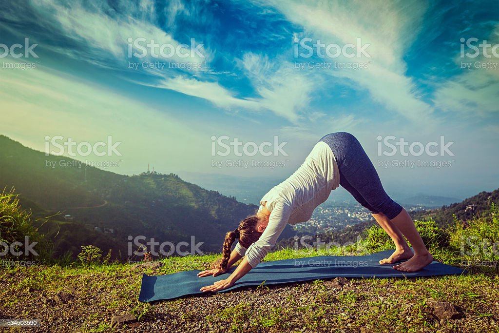 Young sporty fit woman doing yoga oudoors in mountains stock photo