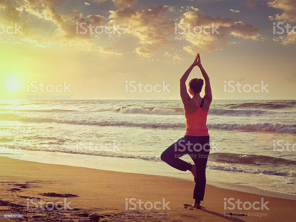 Young sporty fit woman doing yoga tree asana on beach stock photo