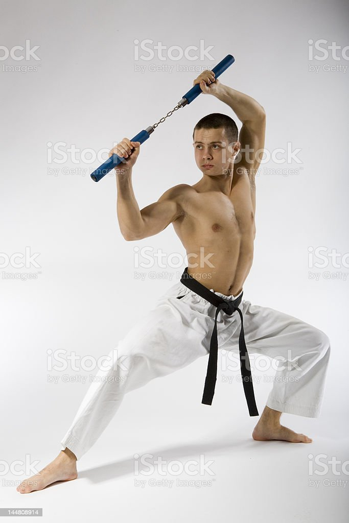 Young sporty karate man doing special exercise on gray background royalty-free stock photo