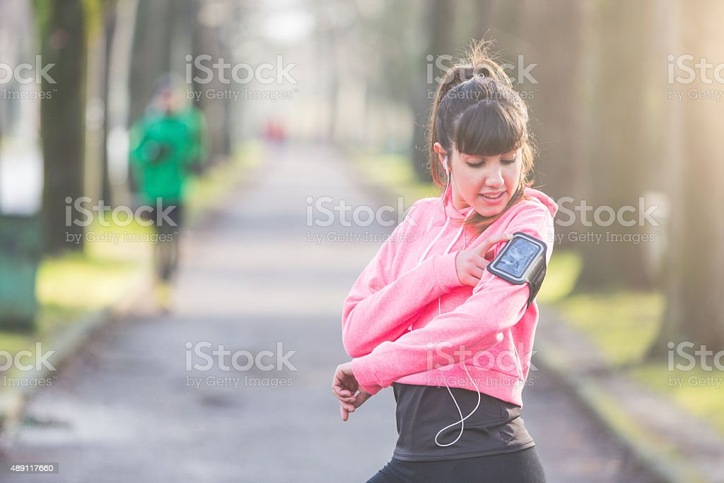 Young sporty woman checking smart phone during workout stock photo