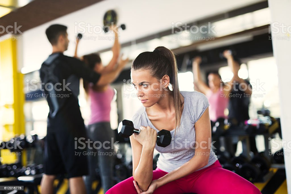 Young sporty woman doing dumbbell exercise at the gym. stock photo