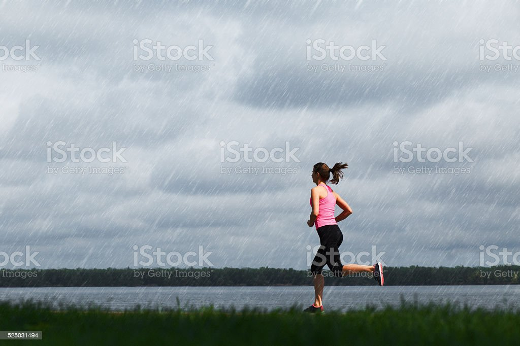 Young sporty woman running at rainy day stock photo