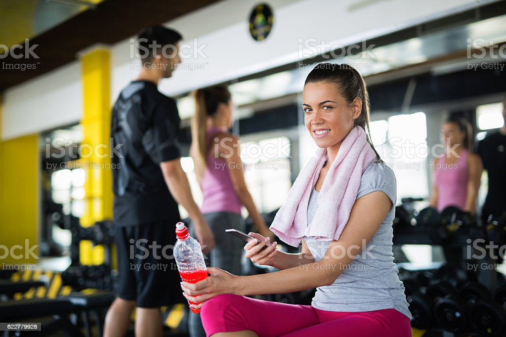 Young sporty woman using mobile phone at the gym. stock photo