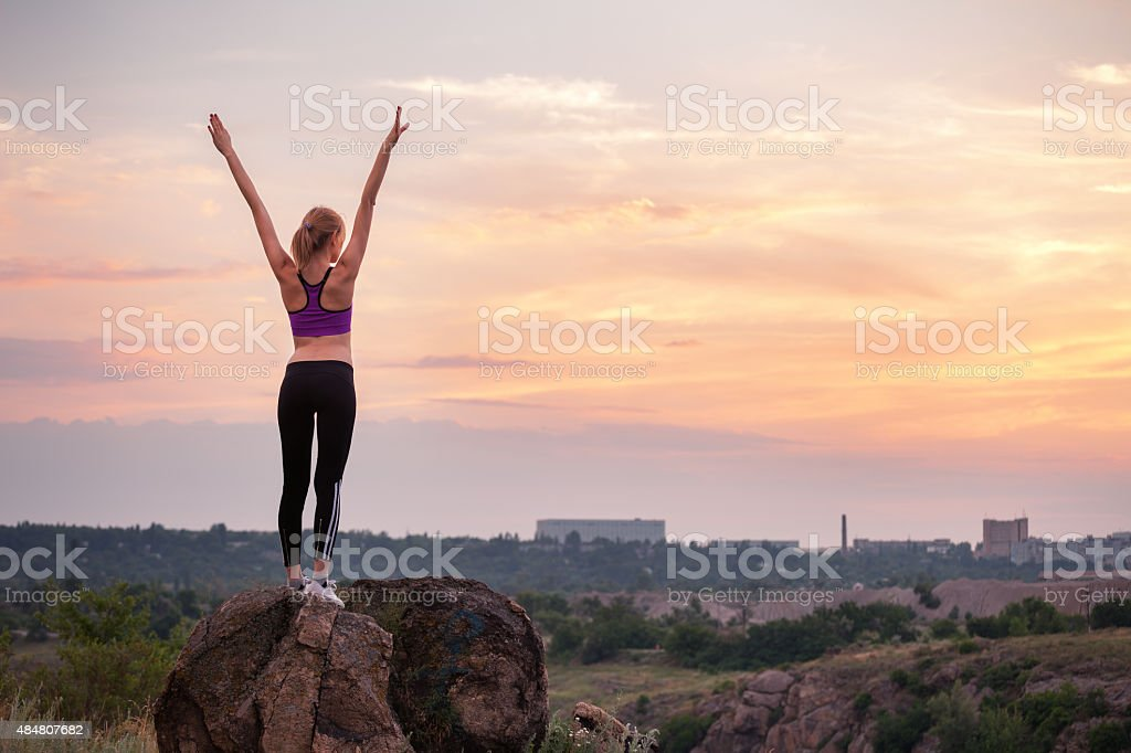 Young sporty woman with arms raised up at sunset stock photo