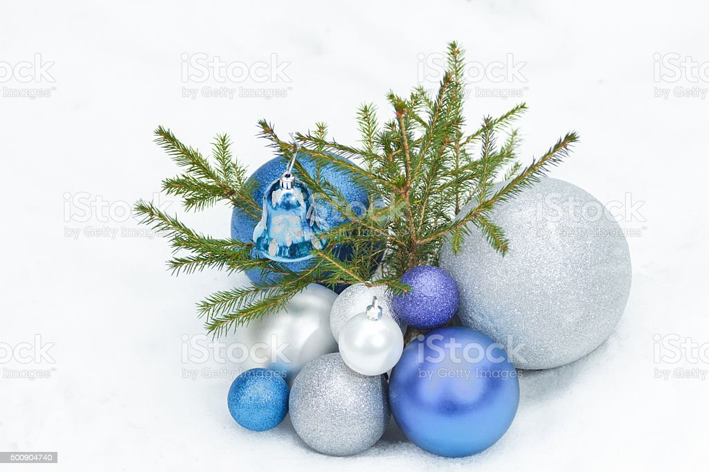 Young spruce tree on snow with Christmas blue ornaments stock photo