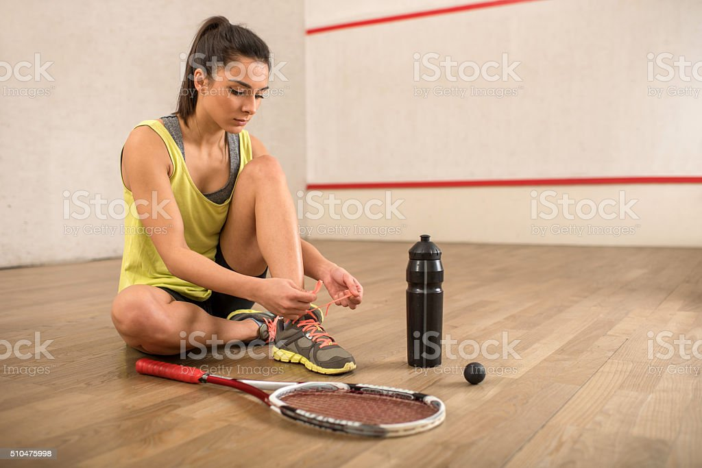 Young squash player tying her shoelaces on a court. stock photo