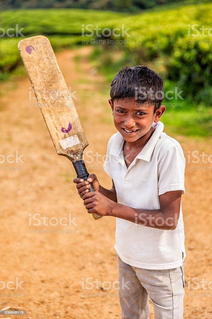 Young Sri Lankan boy playing cricket on tea plantation stock photo