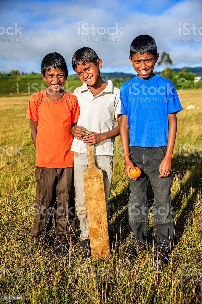 Young Sri Lankan boys playing cricket on tea plantation stock photo