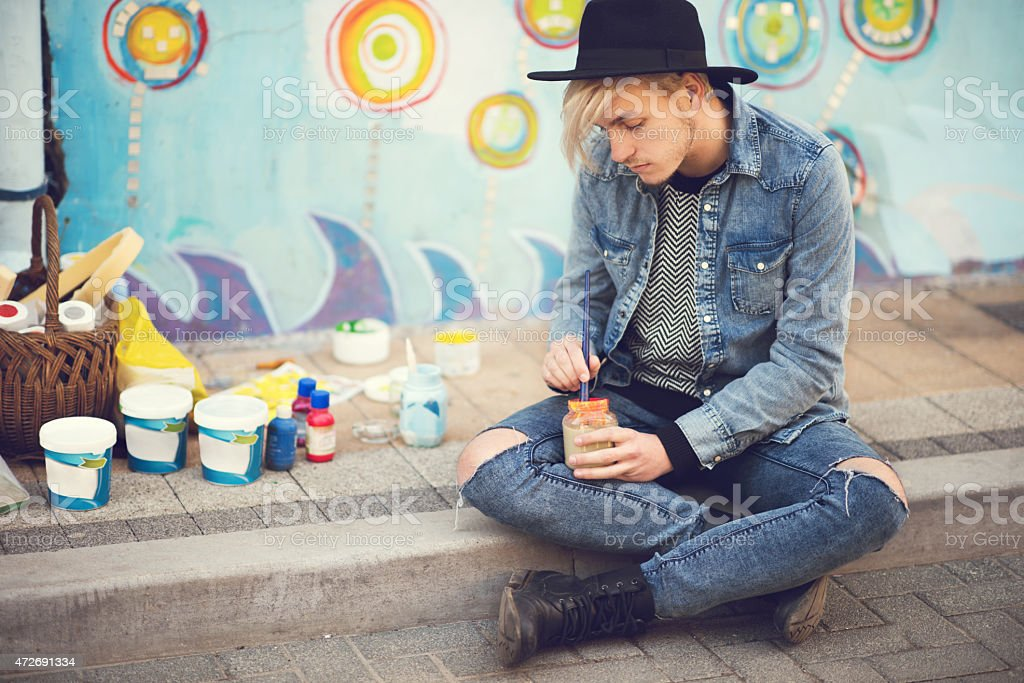Young street artist preparing paint for painting a wall. stock photo