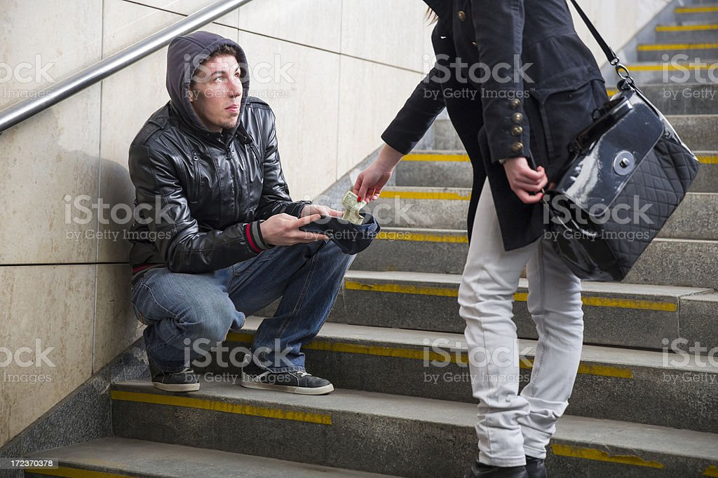 Young street begger...begging on stairway...woman is giving him some cash royalty-free stock photo