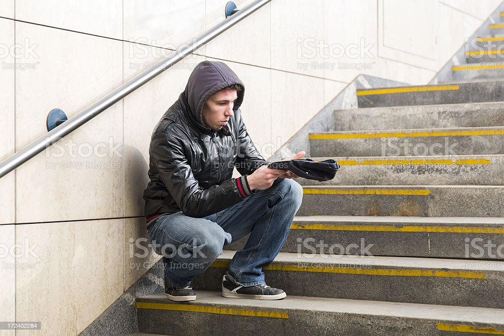 Young street begger...probably an addict, begging on a stairway royalty-free stock photo