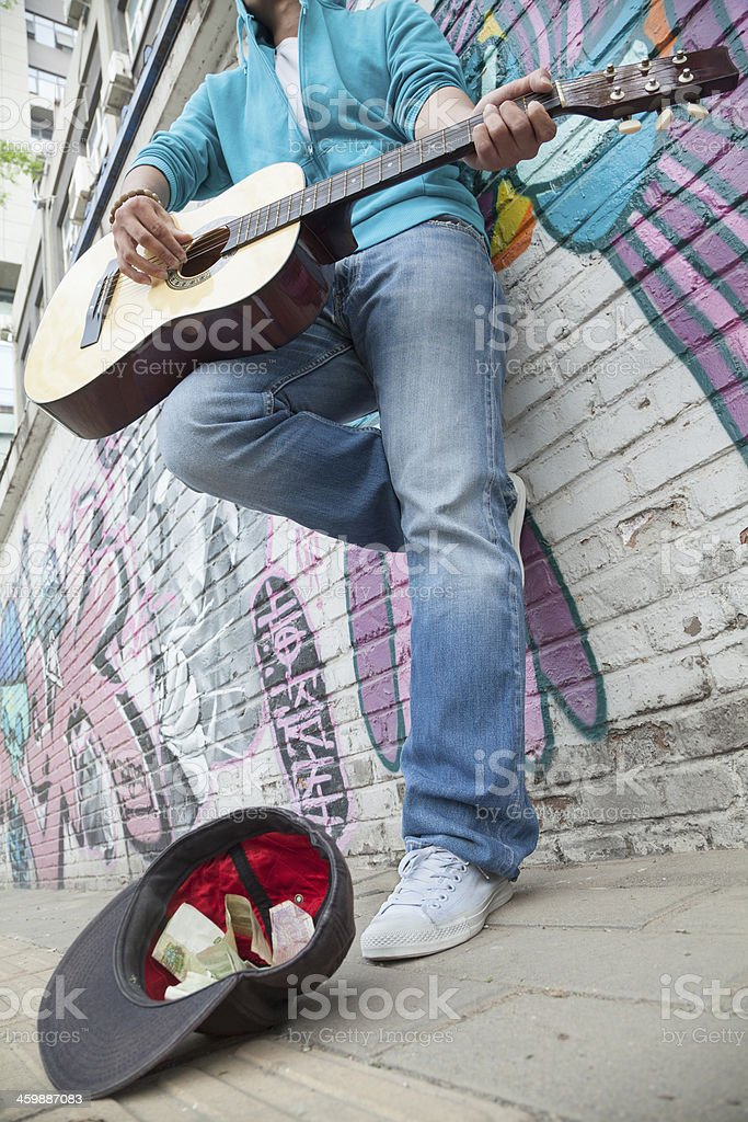Young street musician playing guitar stock photo