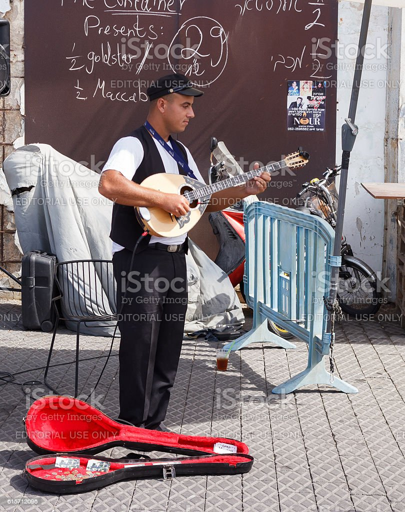 Young street musician playing the lute on the waterfront stock photo