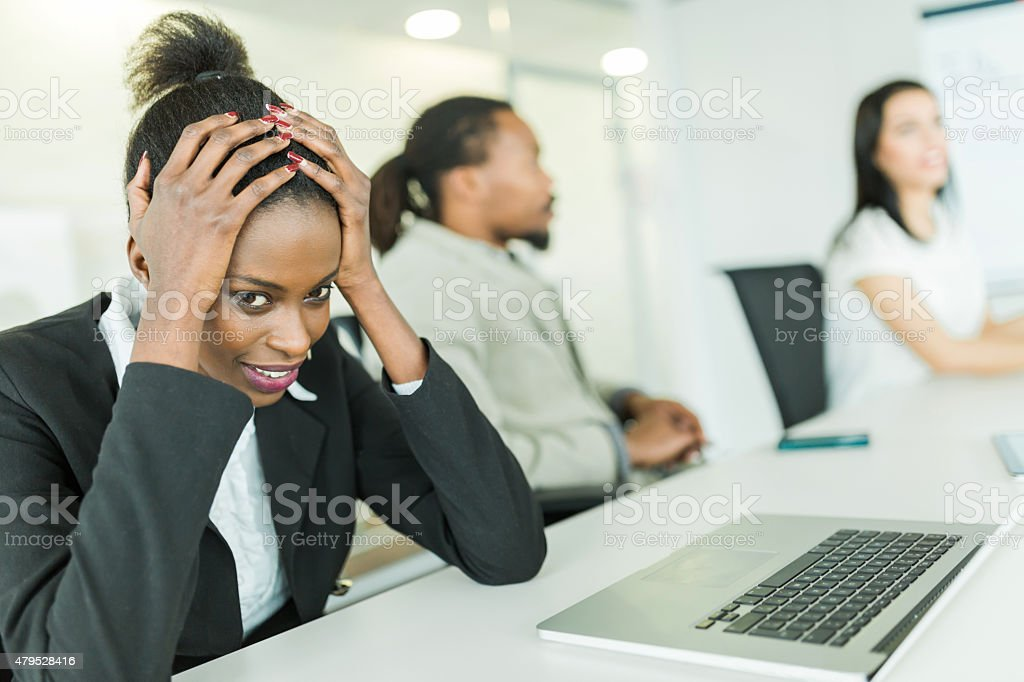 Young stressed businesswoman battling with a headache during a conference stock photo