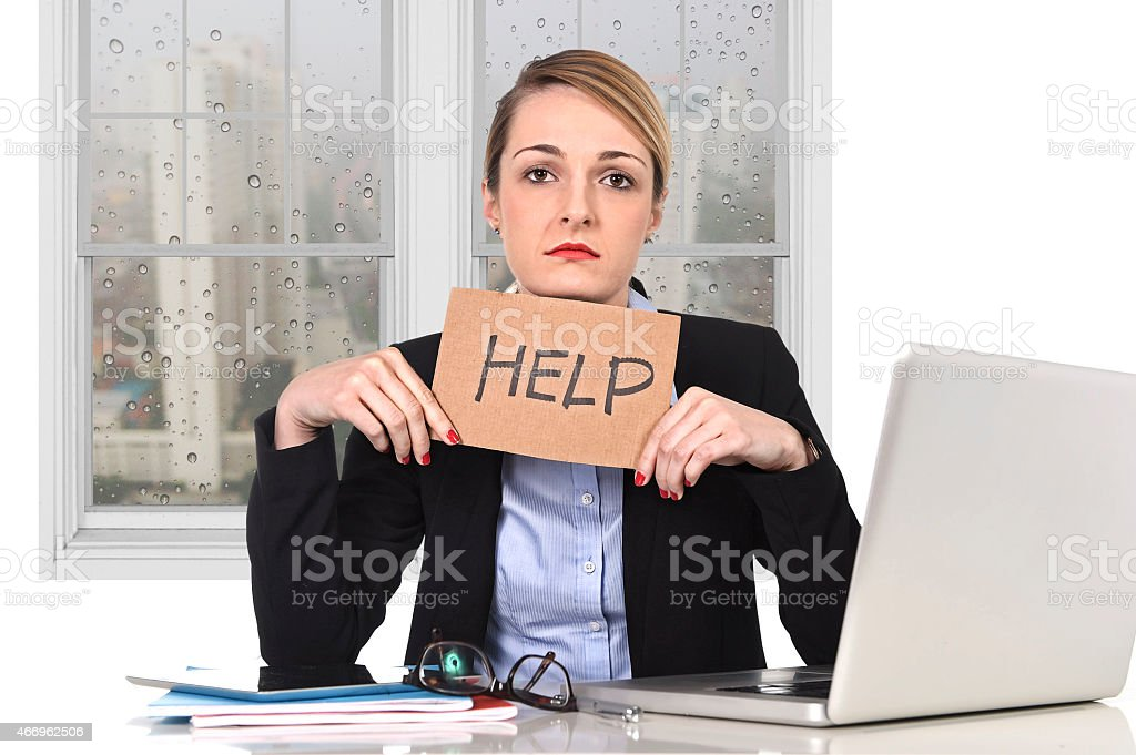 young stressed businesswoman holding help sign overworked at office computer stock photo