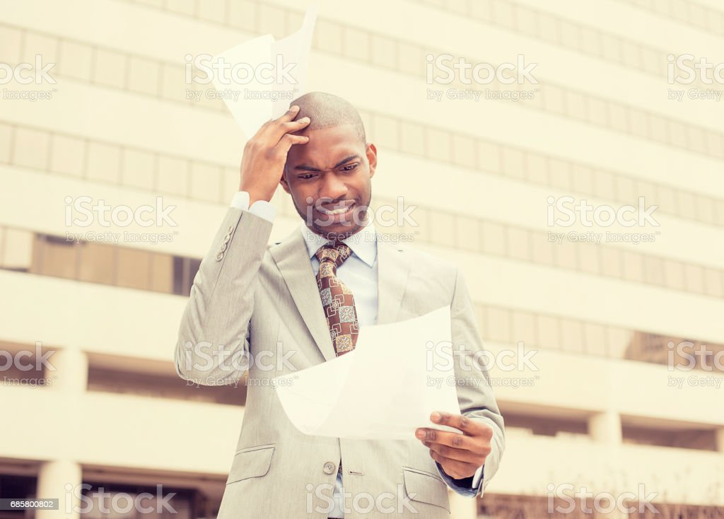 young stressed frustrated man holding looking at documents standing in front of corporate office stock photo