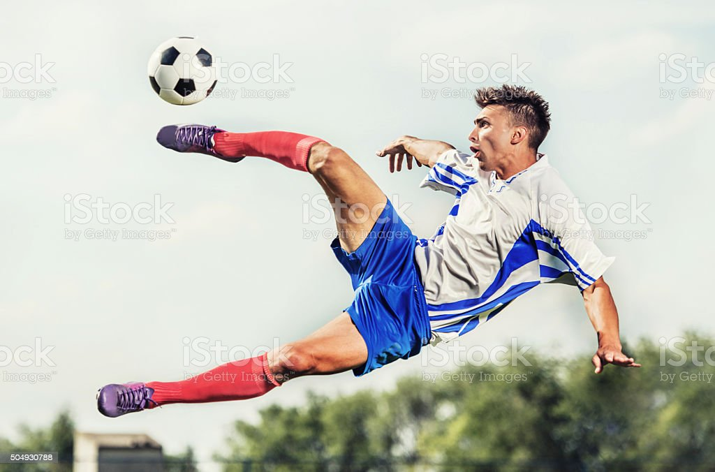 Young striker taking football shot while being in mid air. stock photo