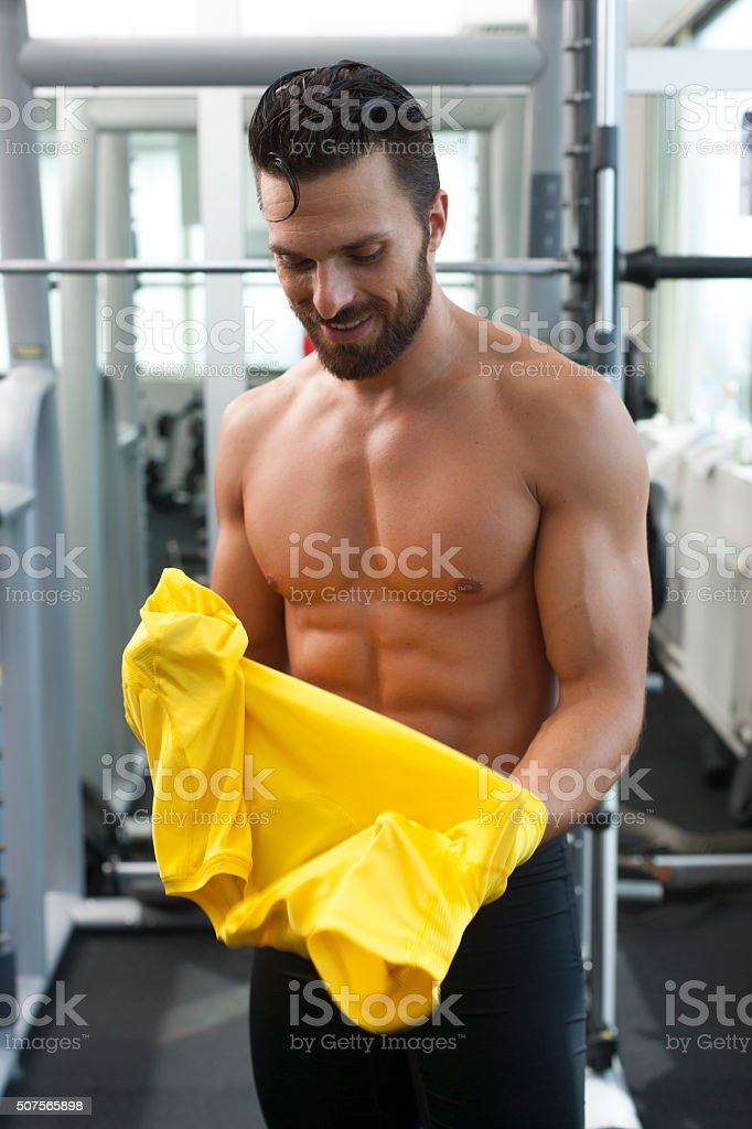 Young strong fit man in gym putting t shirt on stock photo