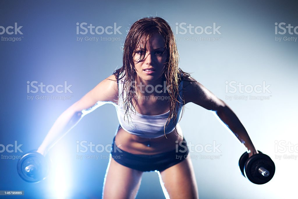 Young strong sexy woman lifting dumbbells in each hand royalty-free stock photo
