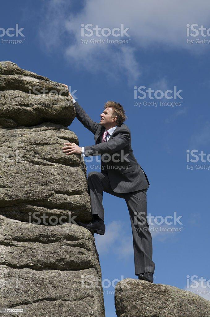 Young Struggling Businessman Climbing a Big Rock Blue Sky royalty-free stock photo