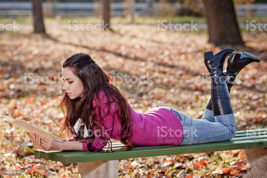 Young studen girl, reading book in the park royalty-free stock photo