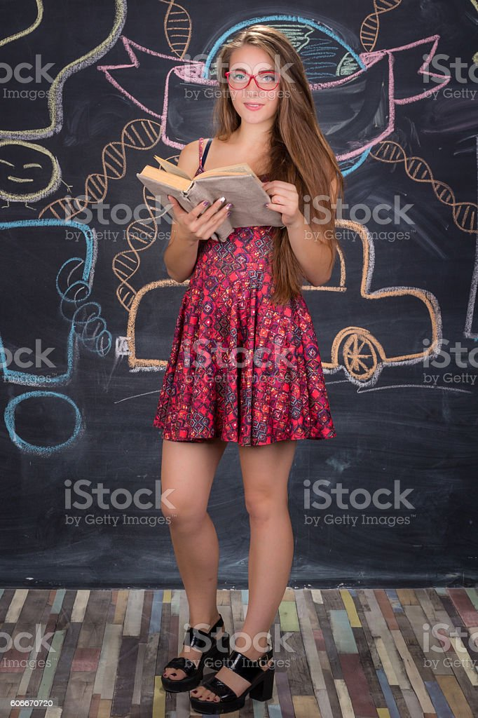 Young student girl in red dress stands and reads book stock photo