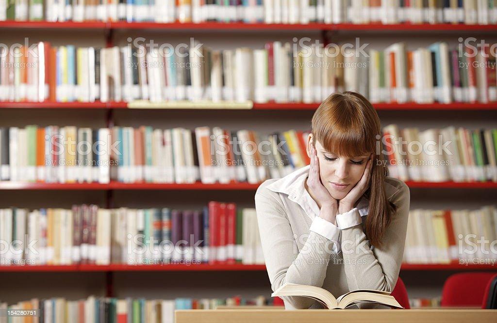 Jeune étudiante dans une bibliothèque photo libre de droits
