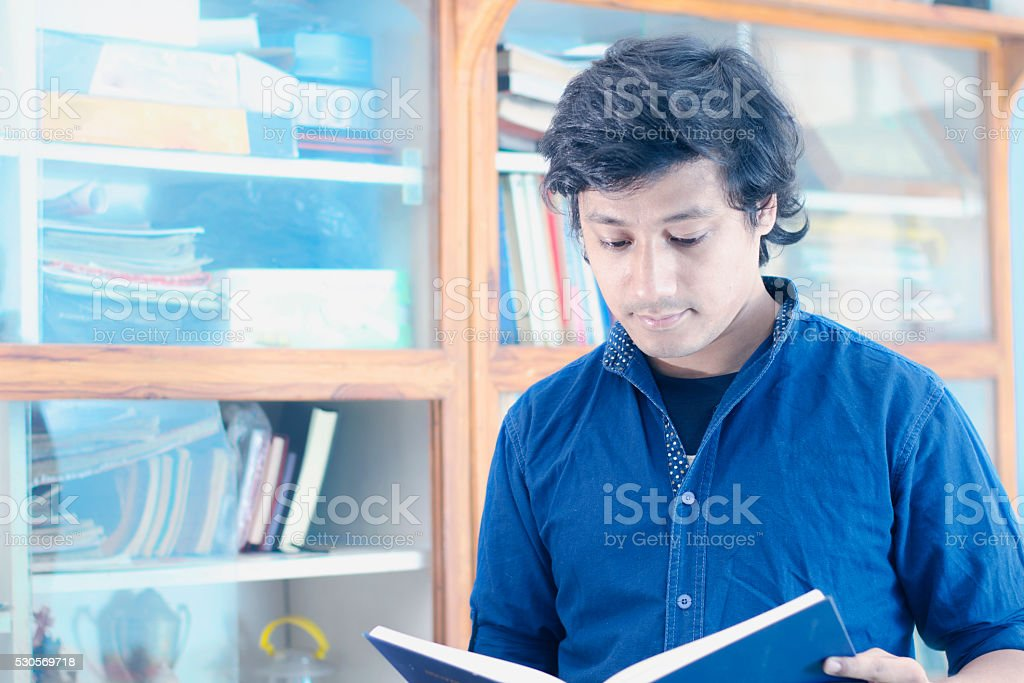 Young student in library reading book stock photo
