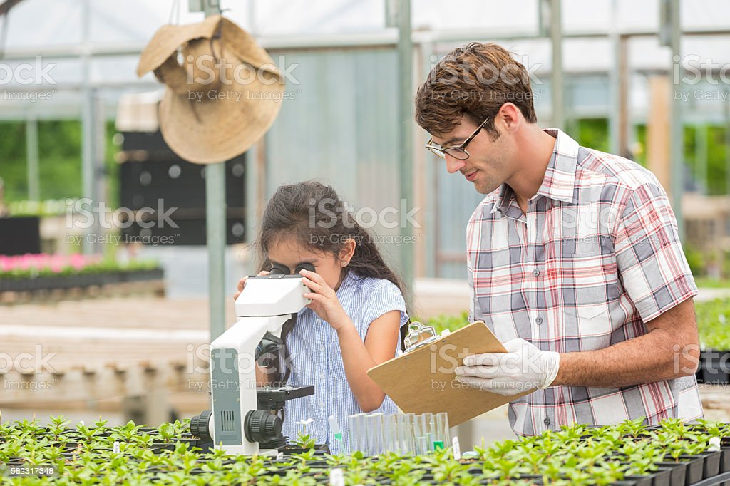 Young student looking into a microscope with teacher stock photo
