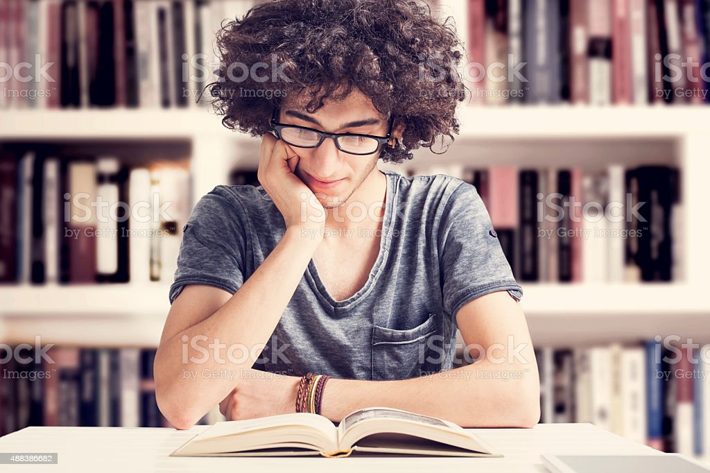 Young student reading  book in library stock photo