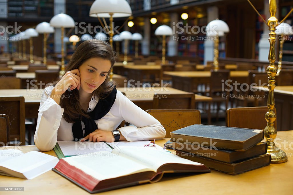 Young student studying in the library royalty-free stock photo
