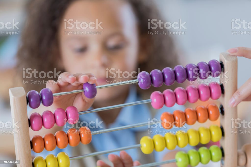 Young student uses abacus at school stock photo