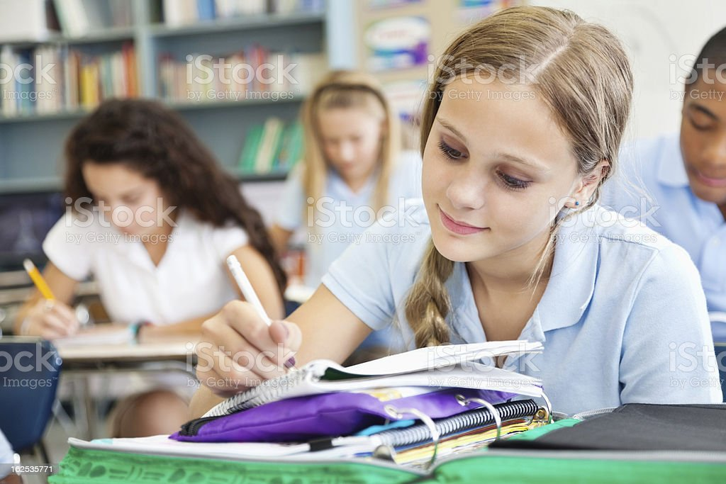 Young student writing in class full of students royalty-free stock photo