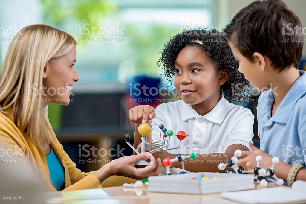 Young students and teacher in science class studying solar system stock photo