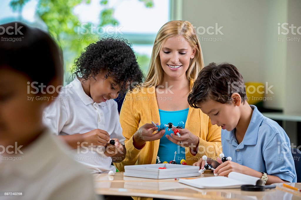 Young students playing with molecule model in science class stock photo