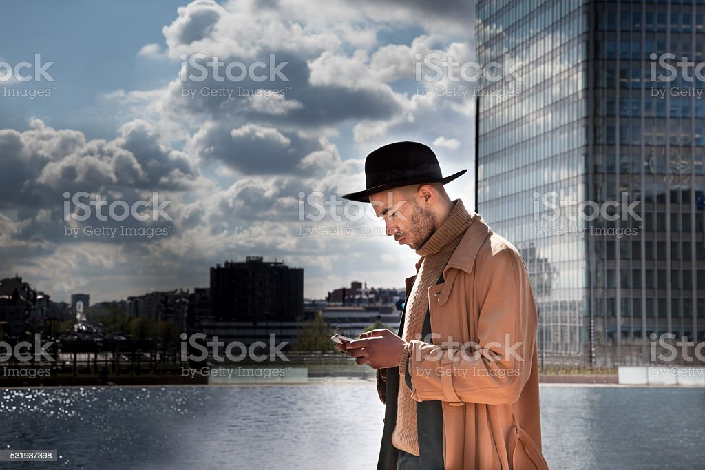 young stylish black businessman consults mobile phone in financial district stock photo