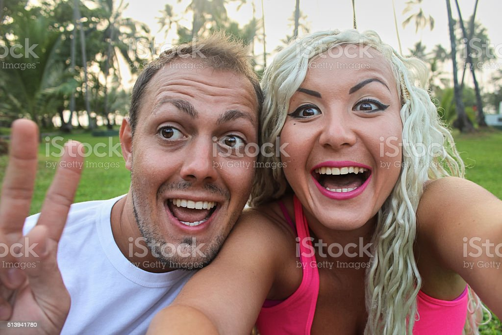 Young stylish funny couple smilling  outdoor, tropical green grass. stock photo