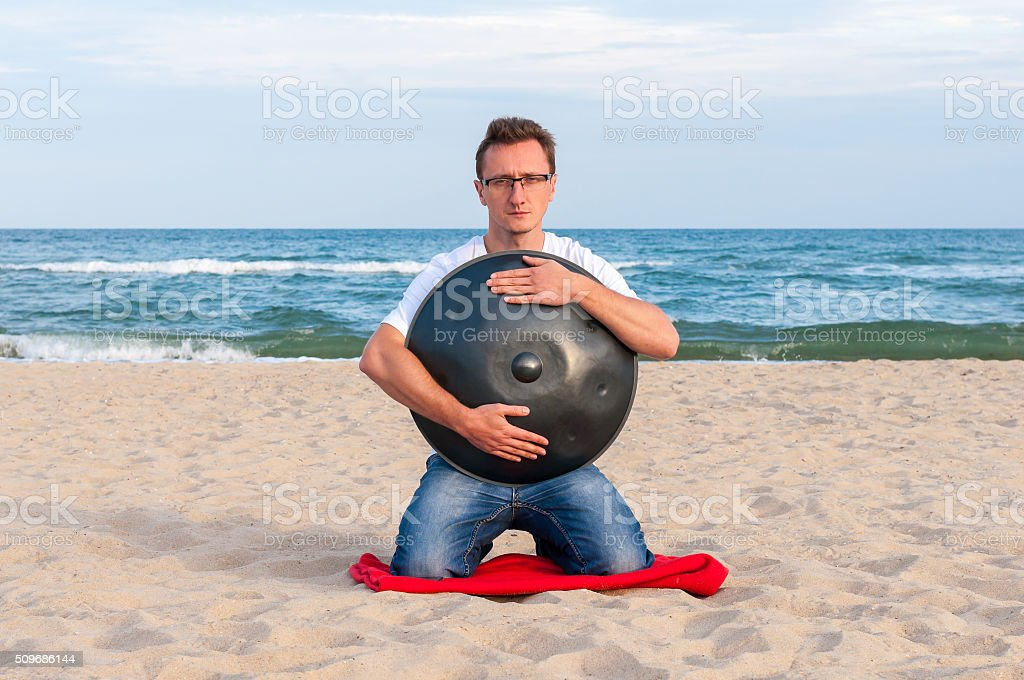 Young stylish guy sitting on the sand beach and holding stock photo