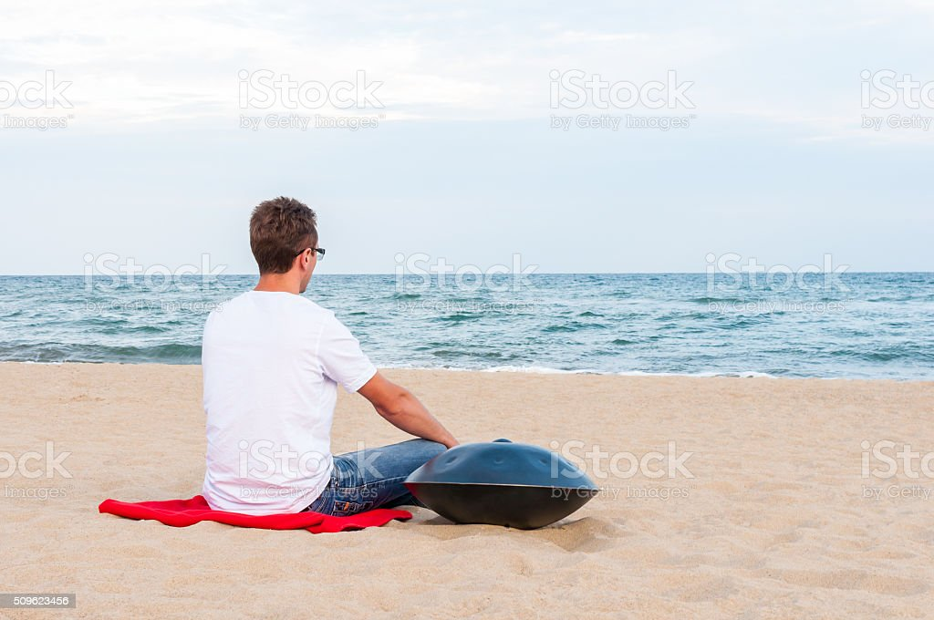 Young stylish guy sitting on the sand beach near handpan stock photo