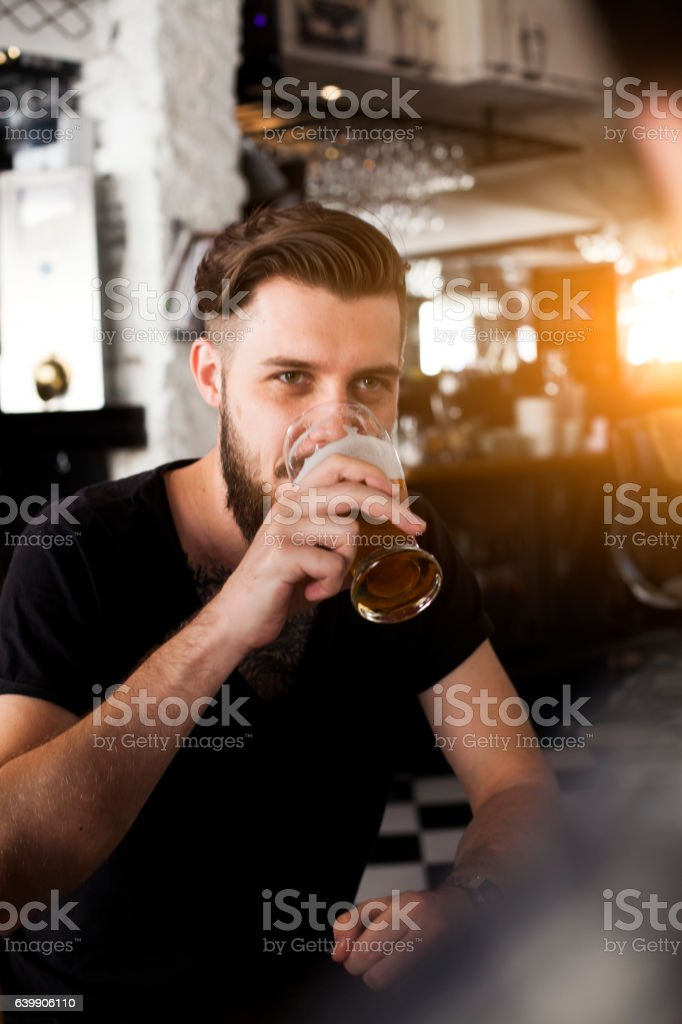 Young stylish man drinking beer stock photo