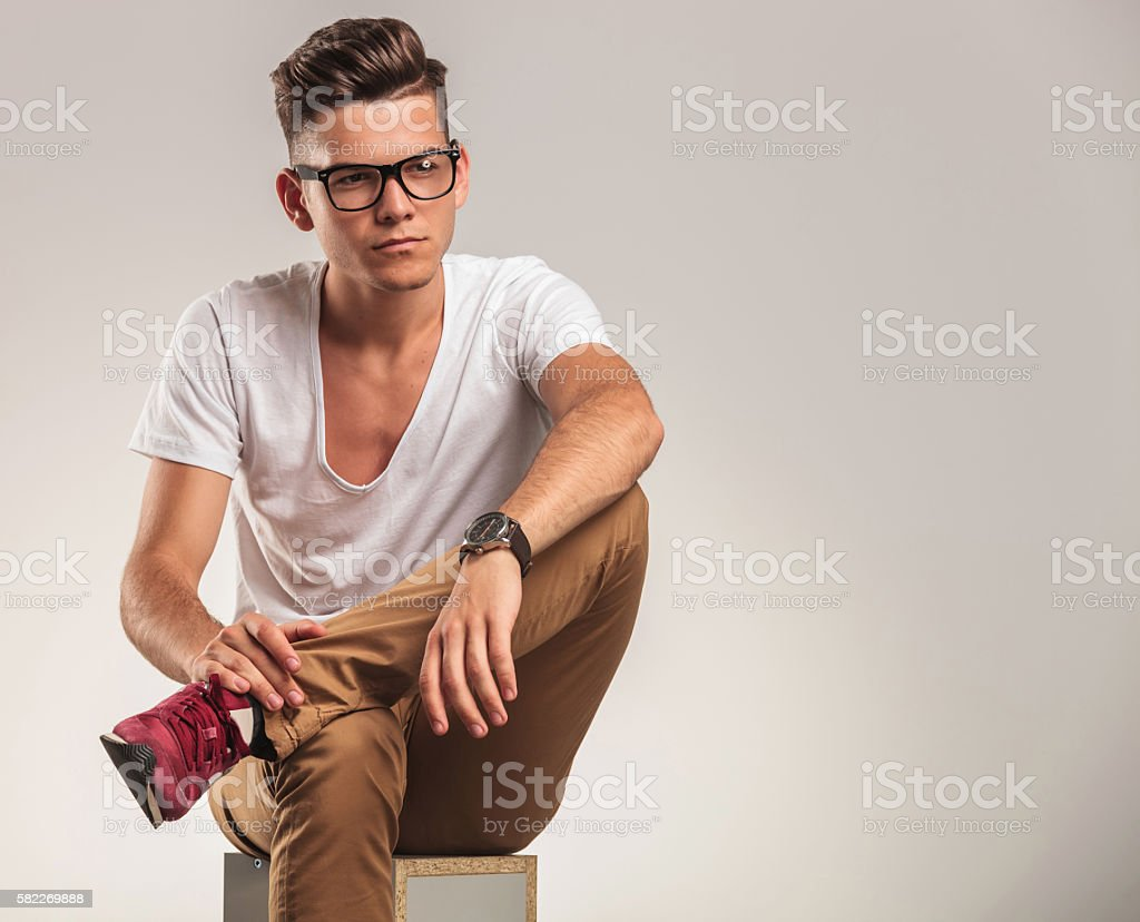 young stylish man looking away while standing stock photo