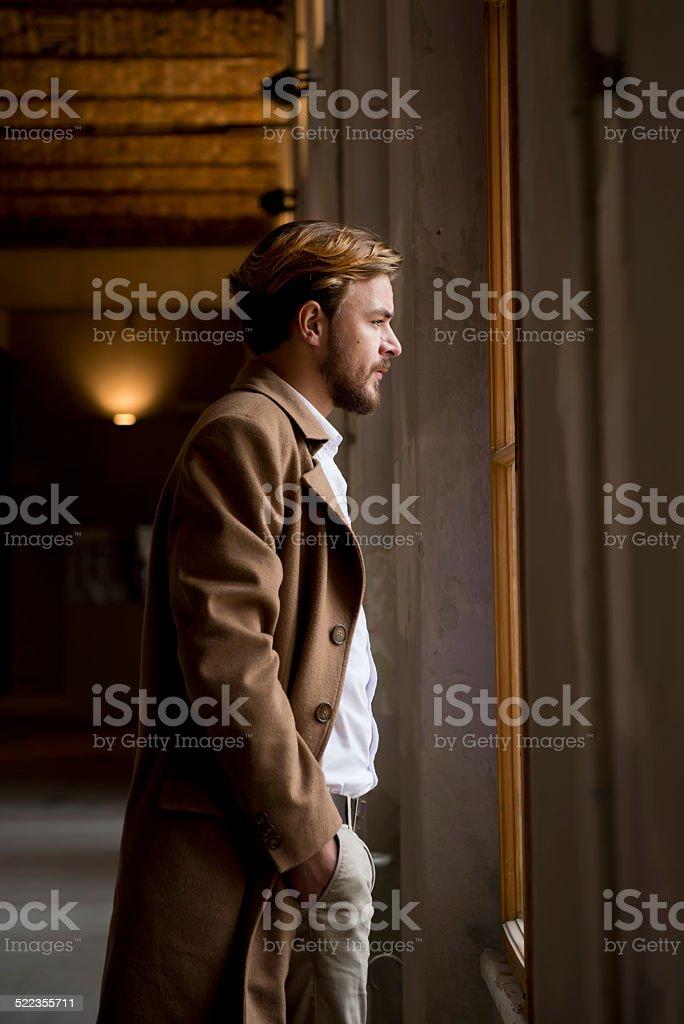 Young stylish man looking thrue window stock photo