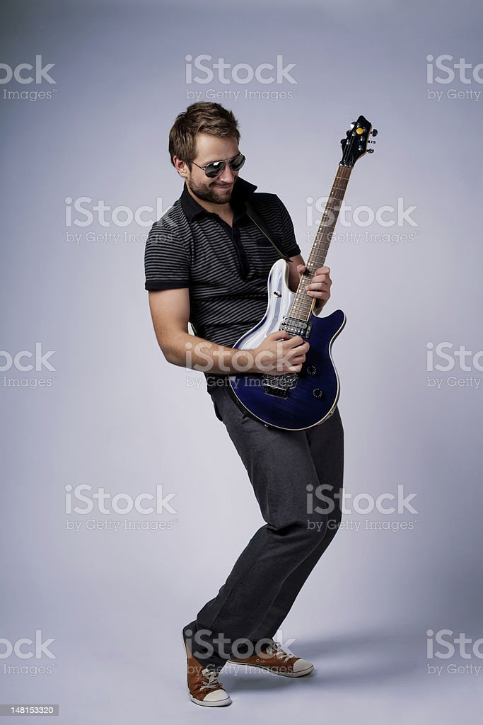 Young stylish man playing an electric guitar stock photo
