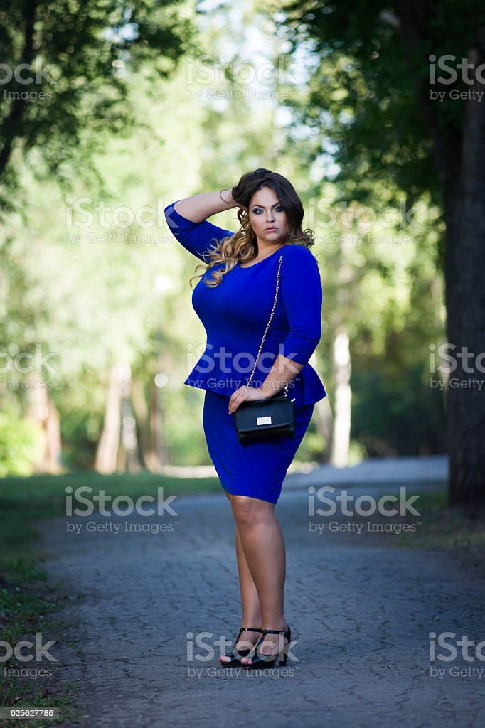 Young stylish plus size fashion model in blue dress outdoors stock photo
