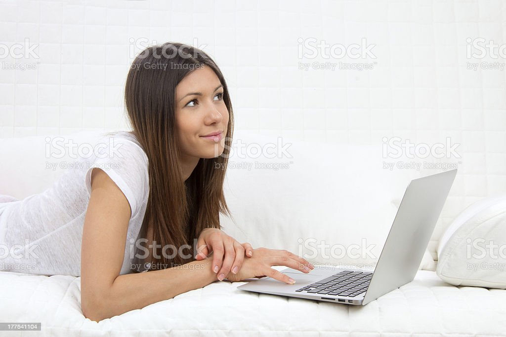 Young succesful woman lying on a sofa with laptop royalty-free stock photo